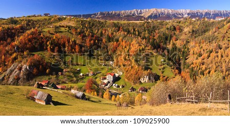 Mountain autumn panorama landscape and village near colorful forest - stock photo