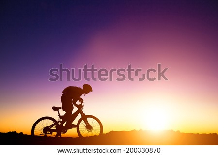 mountain bicycle rider on the hill with sunrise background - stock photo