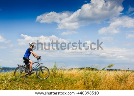 Mountain Bike cyclist riding Meadow track on a sunny day. Healthy lifestyle active athlete
