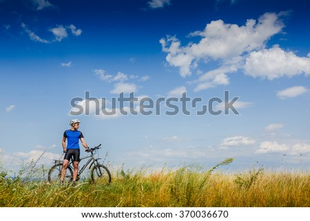 Mountain Bike cyclist riding Meadow track on sunny day. healthy lifestyle active athlete
