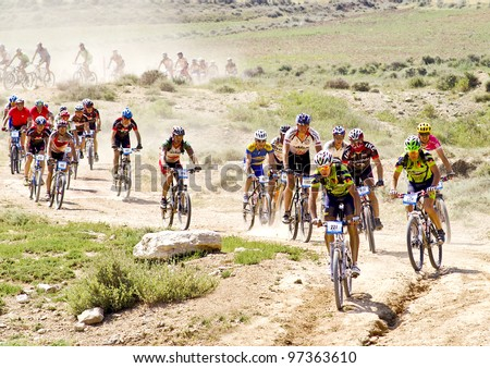 """mountain bike cyclists competing in a race through the nature park dessert """"Las Bardenas"""". Temperature reaches 37ºc on June 28th, 2008, in Tudela, Navarre, Spain. BARDENAS REALES, NAVARRE, SPAIN - stock photo"""
