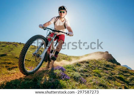 Mountain bike. Man riding bicycle on a dusty trail. Downhill.