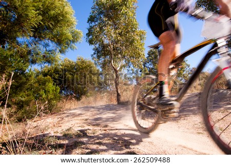 Mountain bike racer zooming past, with motion blur