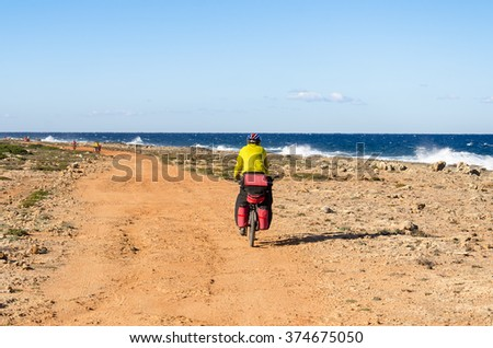 Mountain bike rider on a winding dirt road along the sea - stock photo