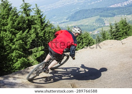 Mountain bike rider rides through a gravity slope of an artificial dirt track. The background shows the black forest in Germany. - stock photo