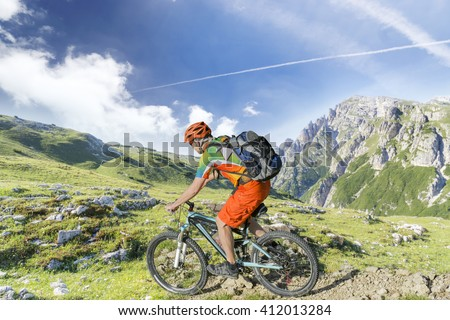 Mountain bike rider with rucksack rides a rocky single trail in the mountains - stock photo