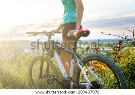 Mountain bike woman looking at the sunset standing on a hill - stock photo