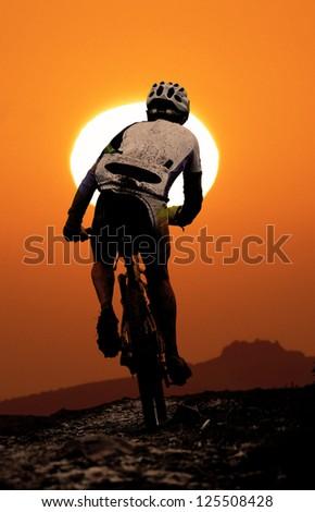Mountain biker agonizes uphill during sunset - stock photo