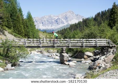 Mountain biker crossing wooden bridge in Swiss mountain area of Graubunnden - stock photo
