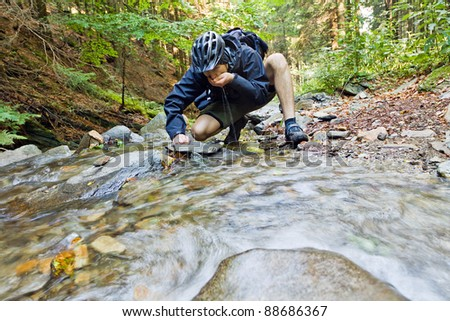 Mountain biker drinking water from a spring