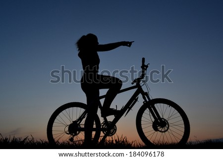 Mountain biker girl silhouette in sunset - stock photo