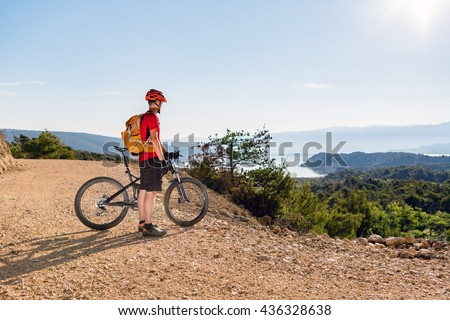Mountain biker looking at the sea, riding on bike in summer landscape. Man rider cycling MTB on country road or single track. Sport fitness motivation, beautiful inspirational view. - stock photo