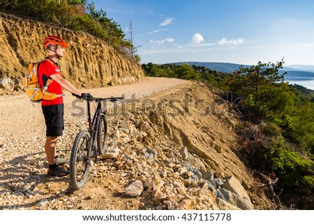 Mountain biker looking at view and riding a bike in summer woods. Man rider cycling MTB on country road or single track. Sport fitness motivation, inspiration in beautiful inspirational landscape. - stock photo