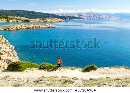 Mountain biker looking at view and traveling on bike in summer sea landscape. Man rider cycling MTB on country road or single track. Fitness motivation, inspiration in beautiful inspirational view. - stock photo