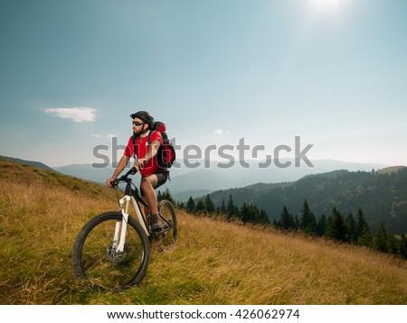 mountain biker on a meadow, enjoying his ride - stock photo
