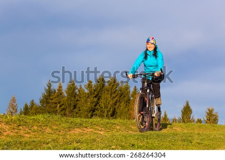 mountain biker on sunny day riding on a winding dirt road in a rural hilly area of green forest against the blue sky with beautiful clouds - stock photo