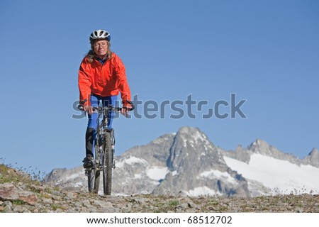 Mountain biker on the road in the Swiss Alps