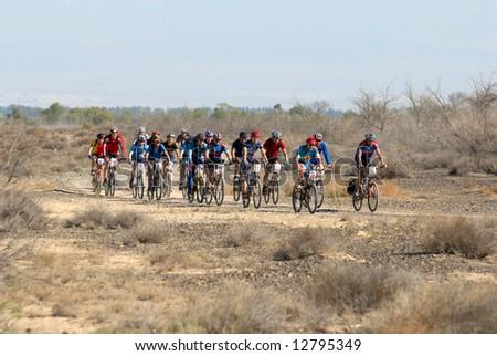 Mountain biker racing on desert road - stock photo