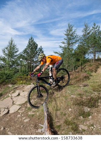 Mountain biker riding  a trail in a mountain bike park in South Wales, UK on a sunny day in the fall - stock photo