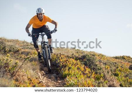 Mountain biker riding dirt trail - stock photo
