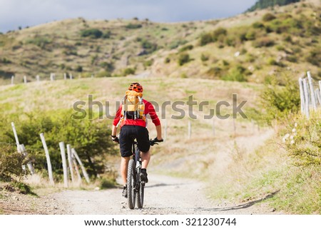 Mountain biker riding enduro on bike in summer mountains landscape. Man MTB adventure cycling with backpack on rural country road. Sport fitness motivation and inspiration. - stock photo