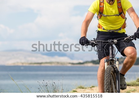 Mountain biker riding on bike at the sea and summer mountains. Man rider cycling MTB on country road or single track. Sport fitness motivation, inspiration in beautiful inspirational landscape. - stock photo
