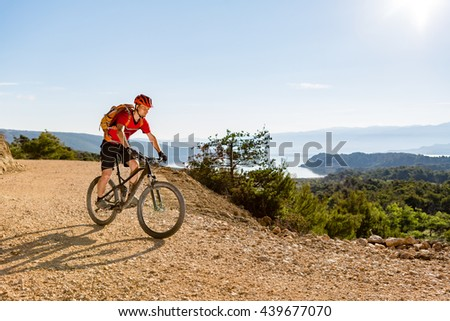 Mountain biker riding on bike at the sea and summer mountains. Man rider cycling MTB on country road or single track. Sport fitness motivation, inspiration in beautiful inspirational landscape.