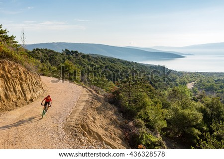 Mountain biker riding on bike at the sea and summer mountains. Man rider cycling MTB on dirt country road or single track. Sport fitness motivation, inspiration in beautiful inspirational landscape. - stock photo