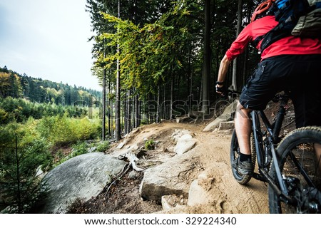 Mountain biker riding on bike in autumn inspirational mountains landscape. Man cycling MTB on enduro trail track. Sport fitness motivation and inspiration. - stock photo