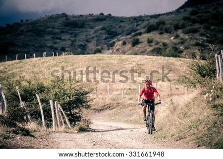 Mountain biker riding on bike singletrack trail in autumn mountains. Man rider cycling MTB on country road or single track. Sport fitness motivation, inspiration in beautiful inspirational landscape. - stock photo