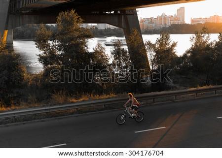 Mountain biker riding through the road traveling - stock photo