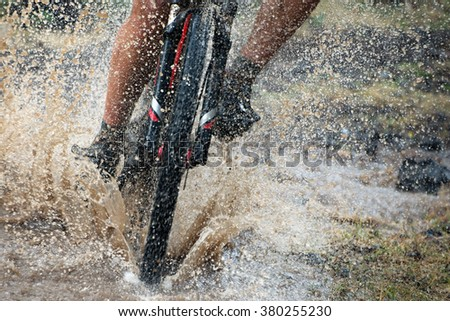 Mountain biker speeding through forest stream. Water splash. - stock photo