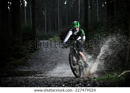 Mountain biker speeding through forest stream. Water splash in freeze motion. - stock photo