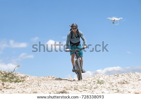 Mountain biker with helmet camera rides a bright gravel road and is followed by a white drone