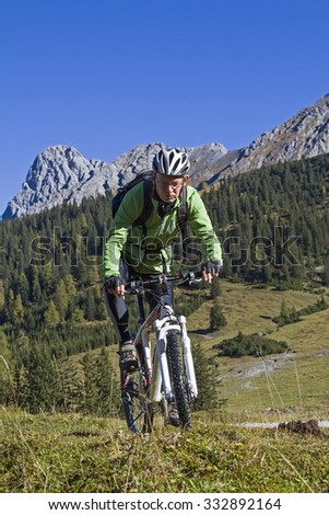 Mountain bikers on the road to Falken hut in karwendel mountains - stock photo