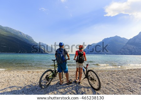 Mountain biking, couple with bikes on Lake Garda, Riva del Garda, Italy