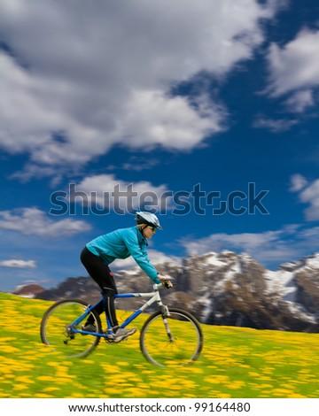 Mountain biking down - woman downhill on bike in dandelion, snowy Dolomites mountain  in the background - stock photo