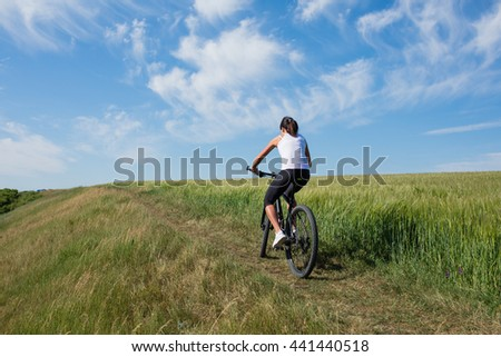 Mountain biking happy sportive girl in white shirt relax in meadows sunny countryside