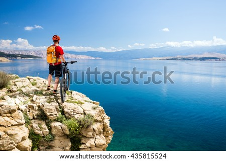 Mountain biking rider with bike looking at inspiring sea and mountains landscape. Man cycling MTB on enduro rocky trail path at sea side. Summer sport, training fitness motivation and inspiration. - stock photo