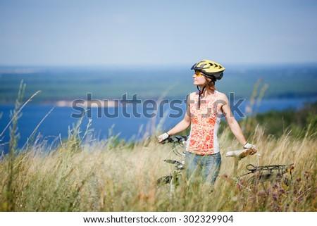 Mountain biking - woman with bike enjoy summer vacation in the beautiful meadow - stock photo