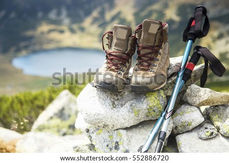 Mountain boots and trekking sticks on mountain peak and lake on background