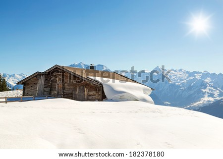 Mountain cabin in winter landscape - stock photo