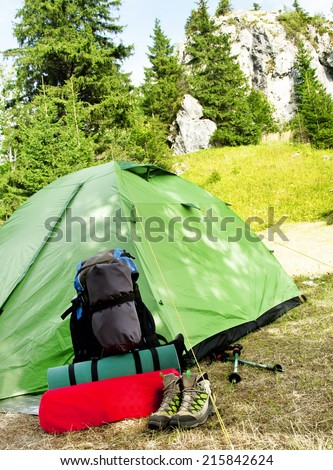 Mountain Camping Equipment with a Tent, Backpack, Trekking Poles and Sleeping Pad on Nature Mountain Background - stock photo