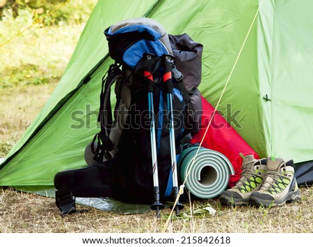 Mountain Camping Equipment with a Tent,Boots, Backpack, Trekking Poles and Sleeping Pad - stock photo