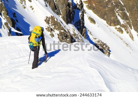 Mountain climber approaching the edge on snow covered summit - stock photo