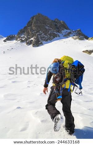 Mountain climber approaching the top  - stock photo