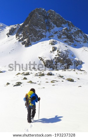 Mountain climber ascends snow covered slope in sunny day