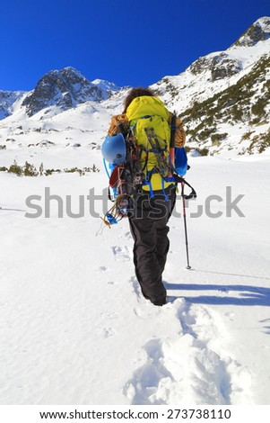 Mountain climber imprinting foot steps on deep snow in sunny day - stock photo