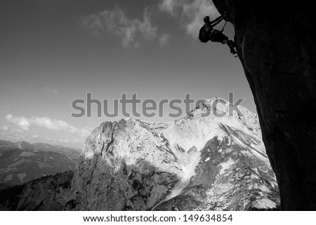 Mountain climber on an overhanging wall above mountain valley.
