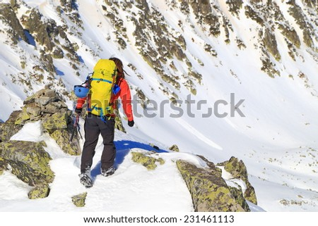Mountain climber scrambling on a snow field in winter